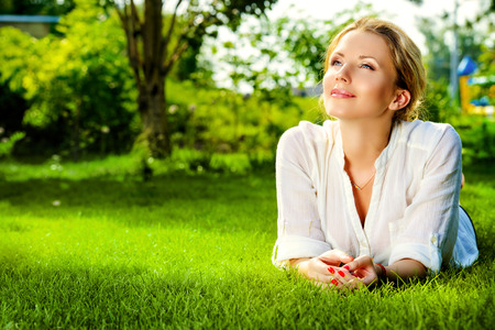 Beautiful smiling woman lying on a grass outdoor. She is absolutely happy.  Archivio Fotografico