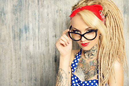 Close-up portrait of a modern pin-up girl wearing old-fashioned polka-dot dress and spectacles and modern dreadlocks. Fashion shot.  Stock Photo