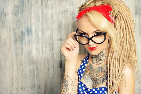 Close-up portret van een moderne pin-up meisje met ouderwetse bolletjes jurk en brillen en moderne dreadlocks. Fashion schot.