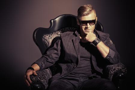 Portrait d'un bel homme masculin dans l'élégant costume noir assis sur une chaise dans un style vintage classique. Banque d'images - 31939260