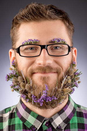 Handsome smiling young man in glasses and a beard of flowers.