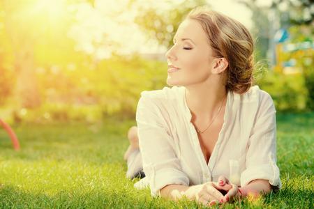 美しい笑顔女性の屋外の芝生の上に横たわる。彼女は絶対に幸せです。 写真素材