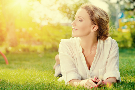 Beautiful smiling woman lying on a grass outdoor. She is absolutely happy. Reklamní fotografie - 32278553
