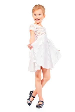 4323d17b61 Foto de archivo - Retrato de cuerpo entero de una niña sonriente linda en  el vestido blanco. Aislado en blanco.