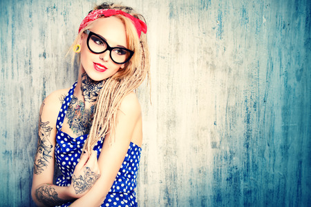 Close-up portrait of a modern pin-up girl wearing old-fashioned polka-dot dress and spectacles and modern dreadlocks. Fashion shot. Tattoo.