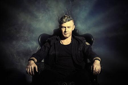 Ritratto di un bel uomo maschile in elegante abito nero, seduta su una sedia in stile classico vintage.