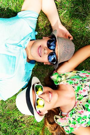放松在草坪的愉快的年轻夫妇在夏天公园。爱概念。假期。