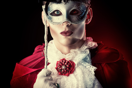 Handsome vampire wearing venetian mask. Halloween carnival. Dracula costume. Stock Photo