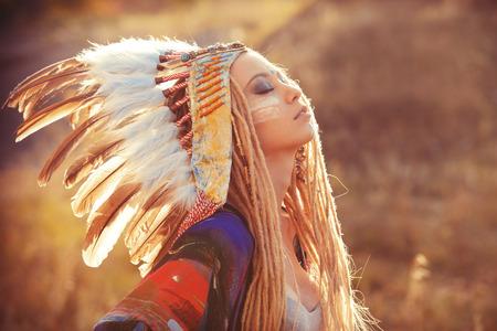 네이티브 아메리칸 인디언 수석 머리 장식을 착용하는 아름 다운 여자의 초상화를 확대합니다. 서양 스타일. 청바지 패션.