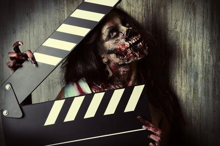 Filmen van een horrorfilm. Vrouwelijke zombie houdt klepel boord. Cinematografie. Halloween. Stockfoto