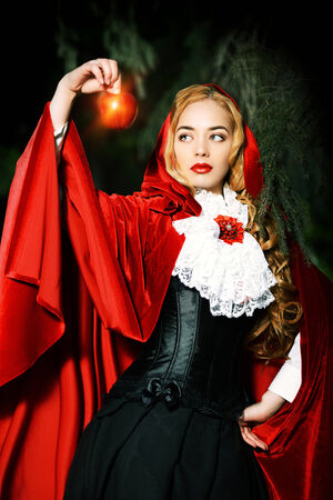 Portrait of a stunning blonde lady in  old-fashioned dress and red cloak in a fairy forest. Фото со стока