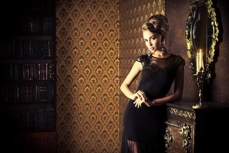빈티지 인테리어에서 포즈 검은 이브닝 드레스에 우아한 젊은 여자. 패션 샷.