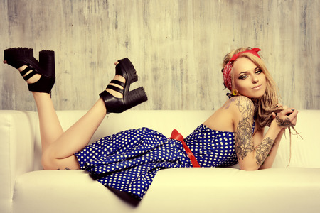 Pretty pin-up girl in old-fashioned polka-dot dress and modern hairstyle dreadlocks. Fashion shot. Mixture of styles.