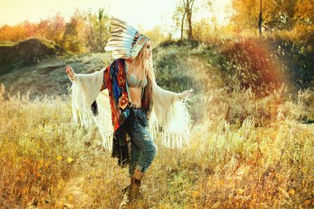아름 다운 소녀가 태양의 광선에 춤을 아메리칸 인디언의 스타일. 서양식. 청바지 패션. 스톡 콘텐츠