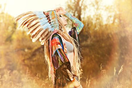 Close-up retrato de una chica hermosa que lleva el tocado jefe indio americano nativo. Estilo occidental. Jeans de moda.