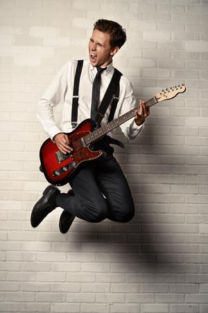 表現力豊かな若者は彼のエレキギターのロック n ロール音楽を再生。レトロ、ビンテージ スタイルです。