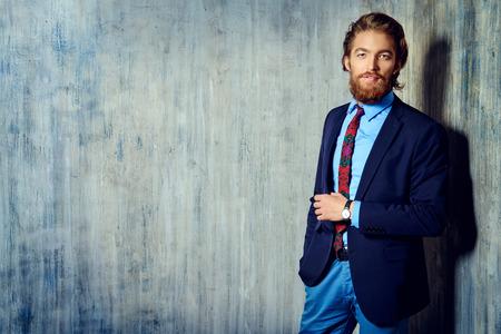 スーツの立派なハンサムな男はカメラに微笑みかけます。男性のファッション。