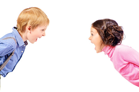 A boy and a girl looking at the camera and shouting. Isolated over white.