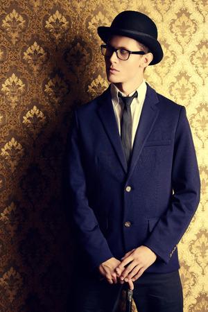 ヴィンテージ背景にポーズ エレガントなスーツと山高帽帽子でハンサムな若い男の肖像画。 写真素材