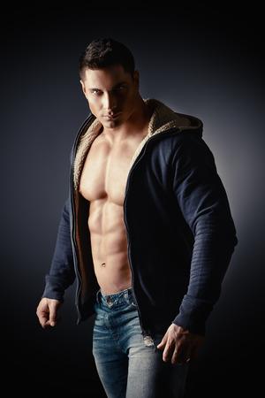 暗い背景上ポーズ セクシーな筋肉青年の肖像画。