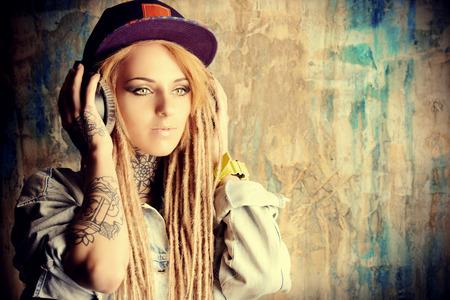 Trendy teenage girl with blonde dreadlocks listening to music on headphones.  Stock Photo