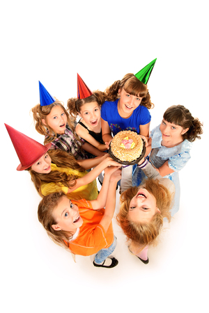 Group of happy kids celebrating birthday with a cake. Isolated over white. Stock Photo