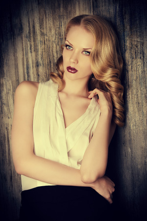 Fashion shot of a glamorous blonde woman with retro make-up and hairdo.