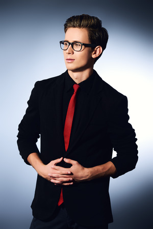 Portrait of a handsome young man in elegant suit and spectacles.