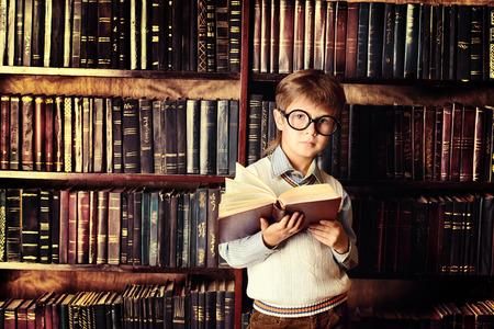 Slimme jongen staat in de bibliotheek door de boekenkast met vele oude boeken. Onderwijs concept. Wetenschap.