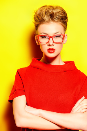 Close-up portrait of a stunning female model in red dress and elegant spectacles posing over yellow background. Beauty, fashion, optics. Фото со стока