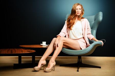 아르누보 스타일의 의자에 앉아 아름다운 패션 모델의 초상화입니다. 인테리어, 가구. 스톡 콘텐츠