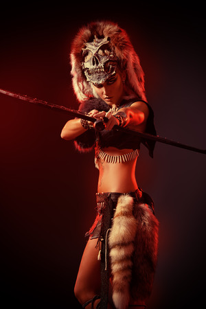 Beautiful bellicose Amazon with bow and arrows in battle. Ancient times. 스톡 콘텐츠