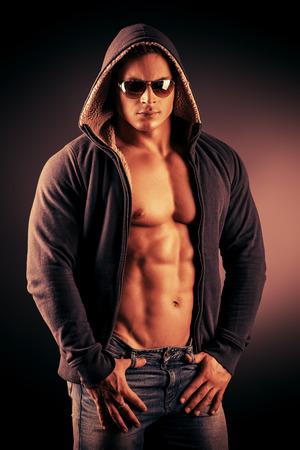 暗い背景にポーズをとってセクシーな筋肉若い男の肖像画。
