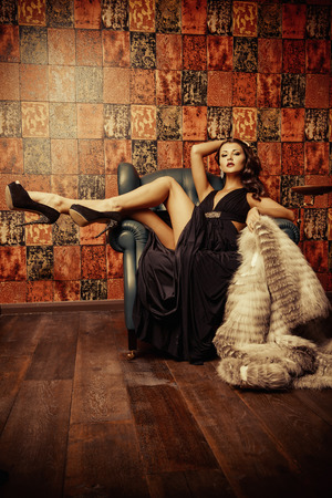 우아한 이브닝 드레스와 모피 코트의 고전적인 실내에서 아름다운 매력적인 여자