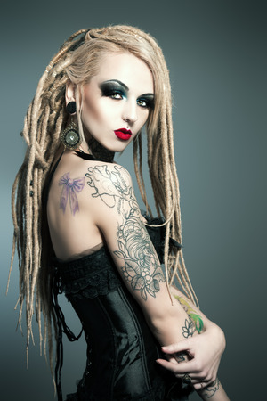 Gorgeous girl with black make-up and long dreadlocks. Gothic style. Fashion. Cosmetics, hairstyle. Tattoo.