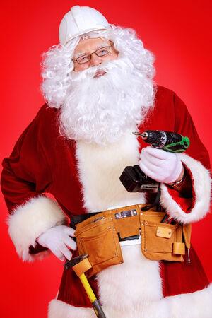Portrait of Santa Claus - builder in helmet builder holding construction tools over red background. Stok Fotoğraf