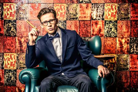 葉巻を吸っているエレガントなスーツでハンサムな若い男。彼は豪華なインテリアで、革張りの椅子に座っています。