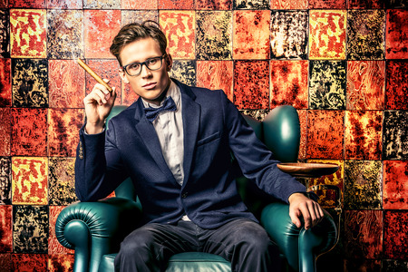 Handsome young man in elegant suit smoking a cigar. He is sitting on a leather chair in a luxurious interior. Stock Photo