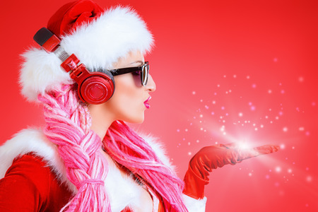 Awesome sexy Christmas girl in headphones. Red background. Christmas party. DJ girl.