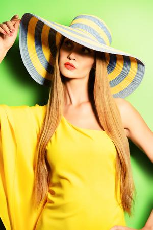 摆在绿色背景的明亮的黄色礼服的一个惊人的时兴的夫人的画象。美,时尚概念。夏天的颜色。