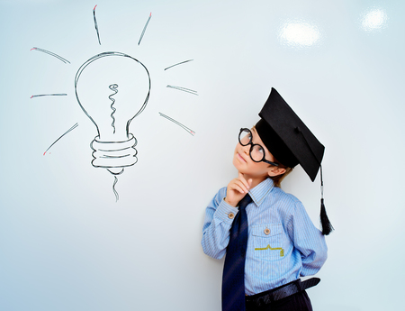 Smart boy stands by the whiteboard in a classroom expressing new idea. Educational concept. Copy space.