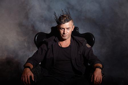 Portrait d'un bel homme masculin dans l'élégant costume noir assis sur une chaise dans un style vintage classique. Banque d'images - 35260866