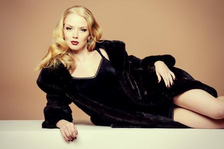 밍크 모피 코트를 입고 아름다운 금발의 여자. 패션, 뷰티. Luxuus 라이프 스타일. 스튜디오 촬영.