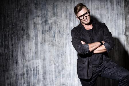 Knappe moderne man in zwart pak en bril staat bij de muur. Mannen beauty, fashion.