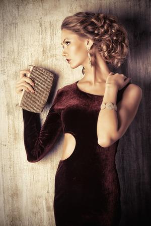 Charmante jonge vrouw, gekleed in elegante avondjurk en mooi kapsel. Sieraden. Mode-shot.