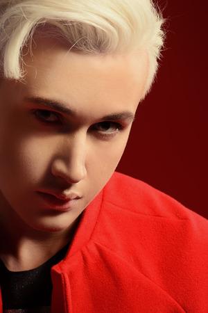 금발 머리를 가진 아름 다운 젊은 남자의 확대 초상화. 남자의 아름다움, 패션. 스톡 콘텐츠