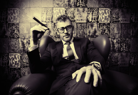 Handsome mature man in elegant suit smoking a cigar. He is sitting on a leather chair in a luxurious interior.