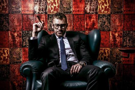 Knappe volwassen man in een elegante pak roken van een sigaar. Hij zit op een leren stoel in een luxueus interieur.