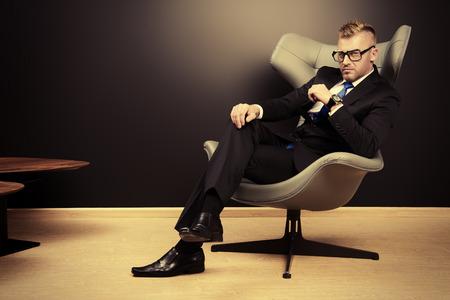 Het opleggen van volwassen man in een elegante pak zittend op een leren stoel in een moderne luxe interieur. Fashion. Business. Stockfoto