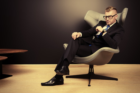 Imposing mature man in elegant suit sitting on a leather chair in a modern luxurious interior. Fashion. Business. Фото со стока